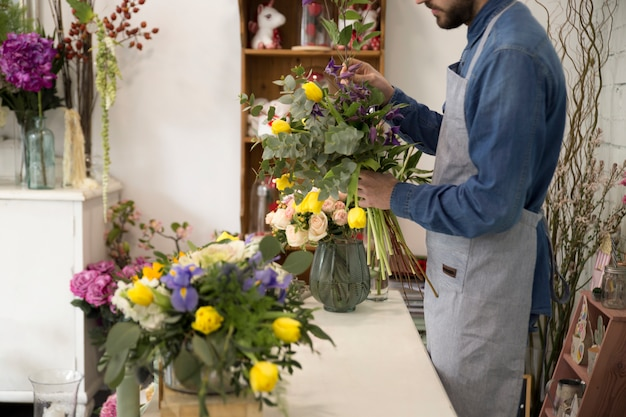 Homem de florista no avental faz um buquê na loja de flores para um presente festivo para um casamento ou aniversário