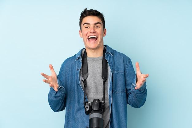 Homem de fotógrafo adolescente na parede azul infeliz e frustrado com algo