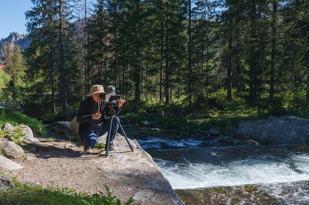Homem de fotógrafo de viagens com a câmera no tripé na floresta, filmando nos bastidores