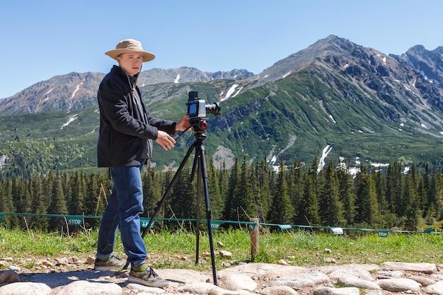 Homem de fotógrafo de viagens com câmera profissional em tripé nas montanhas