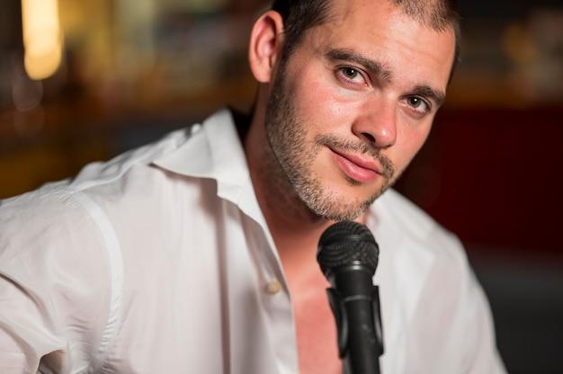 Homem de frente cantando no microfone em uma barra desfocada