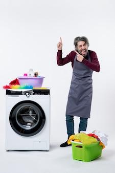 Homem de frente exultante governanta em pé perto do cesto de roupa suja da máquina de lavar em fundo branco
