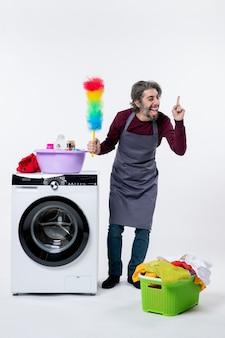 Homem de frente exultante governanta segurando o espanador em pé perto do cesto de roupa suja da máquina de lavar no fundo branco