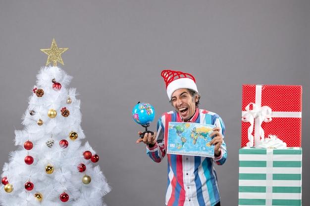 Homem de frente exultante segurando mapa-múndi e globo