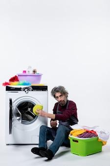 Homem de frente, governanta colocando roupa na máquina de lavar, em fundo branco