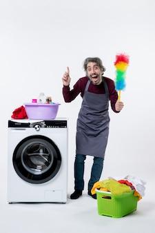 Homem de frente, governanta segurando o espanador em pé perto do cesto de roupa suja da máquina de lavar roupa no fundo branco