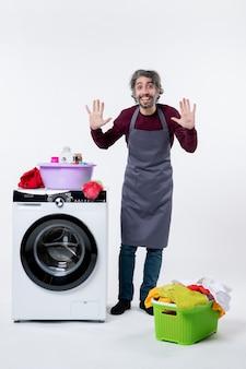 Homem de frente para a governanta levantando as mãos no cesto de roupa suja no chão