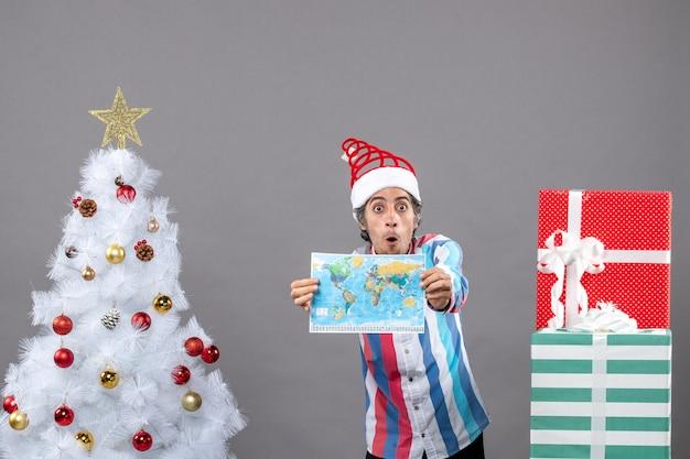 Homem de frente para a surpresa com chapéu de papai noel com mola espiral mostrando o mapa do mundo