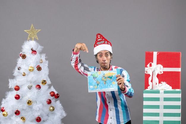 Homem de frente para a surpresa com chapéu de papai noel em espiral apontando para o mapa do mundo