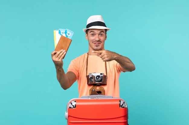 Homem de frente para as férias segurando os ingressos no azul
