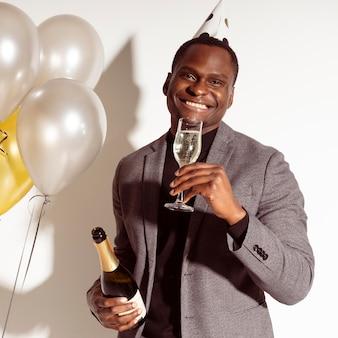 Homem de frente para uma taça de champanhe