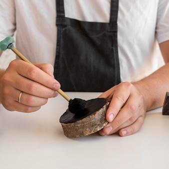 Homem de frente pintando letras de madeira close-up