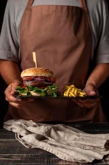 Homem de frente segurando a bandeja com hambúrguer e batatas fritas