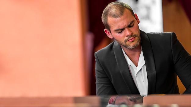 Homem de frente sentindo o piano clássico copiar o espaço