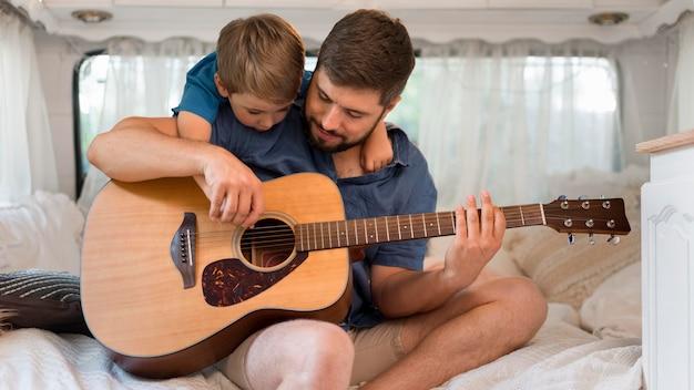 Homem de frente tocando violão em uma caravana ao lado de seu filho