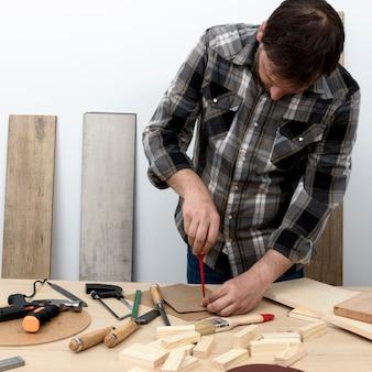 Homem de frente, tomando medidas, conceito de oficina de carpintaria