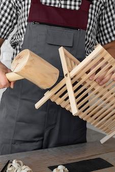 Homem de frente trabalhando em um objeto de madeira