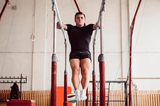 Homem de frente treinando em barras paralelas