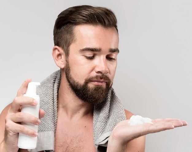 Homem de frente usando creme de barbear