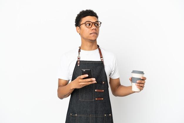 Homem de garçom afro-americano isolado no fundo branco segurando um café para levar e um celular enquanto pensava em algo