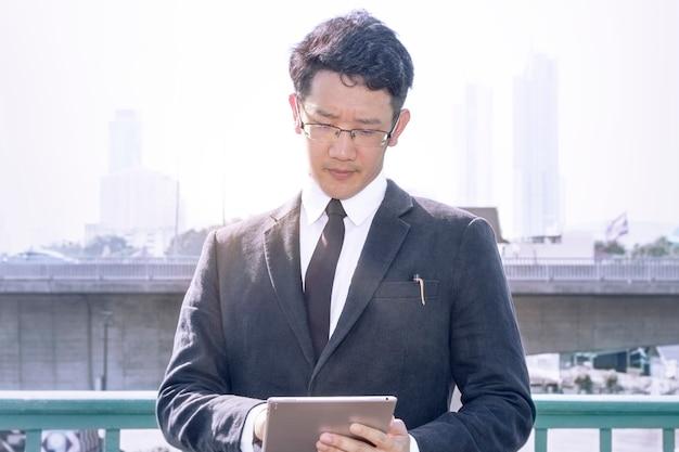 Homem de gerente de negócios com tablet na suite preta e óculos.