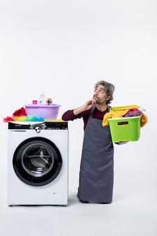 Homem de governanta confuso de vista frontal ajoelhando-se perto da máquina de lavar, segurando o cesto de roupa suja no fundo branco