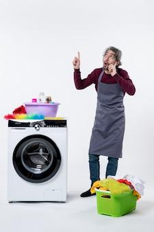 Homem de governanta confuso de vista frontal em pé perto do cesto de roupa suja da máquina de lavar em fundo branco