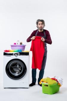 Homem de governanta confuso de vista frontal segurando uma toalha em pé perto da máquina de lavar no fundo branco