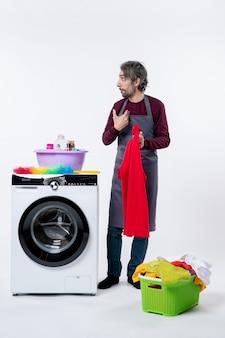 Homem de governanta confuso de vista frontal segurando uma toalha vermelha em pé perto da máquina de lavar no fundo branco