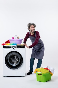 Homem de governanta de frente colocando as mãos no cesto de roupa suja da máquina de lavar no chão