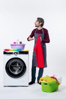Homem de governanta de vista frontal apontando para uma toalha vermelha em pé perto da máquina de lavar, em fundo branco