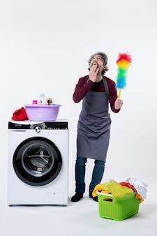Homem de governanta de vista frontal olhando para cima segurando o espanador perto da máquina de lavar no fundo branco
