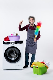 Homem de governanta de vista frontal segurando o espanador em pé perto do cesto de roupa suja da máquina de lavar em fundo branco isolado
