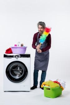 Homem de governanta de vista frontal segurando um espanador perto do cesto de roupa suja da máquina de lavar roupa em fundo branco