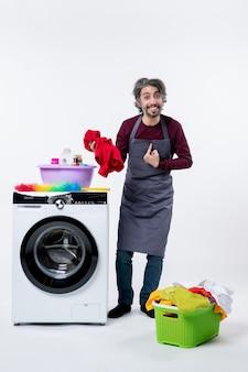 Homem de governanta de vista frontal segurando uma toalha vermelha apontando para si mesmo perto da máquina de lavar no fundo branco