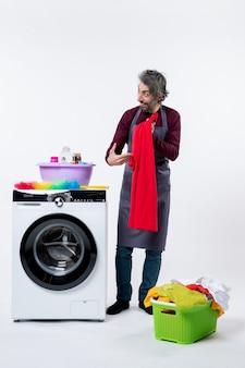 Homem de governanta de vista frontal segurando uma toalha vermelha em pé perto da máquina de lavar no fundo branco