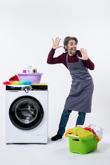 Homem de governanta engraçado de vista frontal em pé perto do cesto de roupa suja da máquina de lavar em fundo branco
