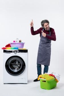 Homem de governanta exultante de vista frontal apontando com o dedo em pé perto do cesto de roupa suja da máquina de lavar no fundo branco