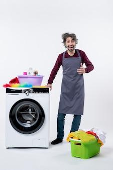 Homem de governanta feliz de vista frontal em pé perto do cesto de roupa suja da máquina de lavar em fundo branco