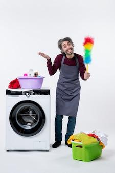 Homem de governanta feliz de vista frontal segurando o espanador em pé perto do cesto de roupa suja da máquina de lavar no fundo branco