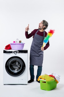Homem de governanta interessado, de frente, segurando o espanador em pé perto do cesto de roupa suja da máquina de lavar no fundo branco
