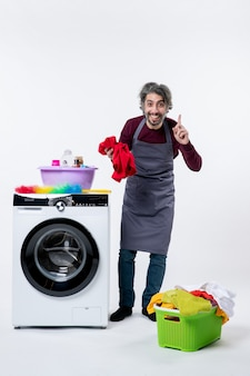 Homem de governanta sorridente segurando uma toalha vermelha em pé perto da máquina de lavar na parede branca de frente