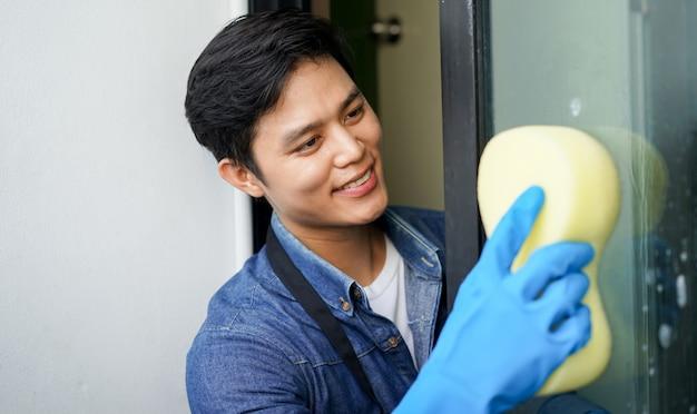 Homem de governanta sorrindo com esponja de exploração para lavar e escovar a janela de poeira no espelho