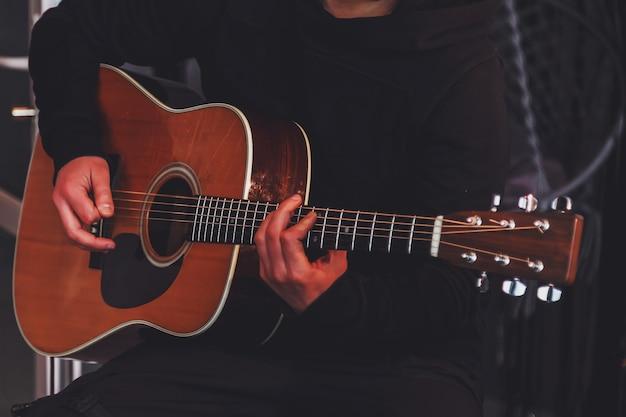 Homem de guitarra segurando nas mãos e jogadores violão. jogando para o conceito de música. jogue ao vivo em casa para o público durante a quarentena e o bloqueio de isolamento devido ao coronavírus. copie o espaço para o site