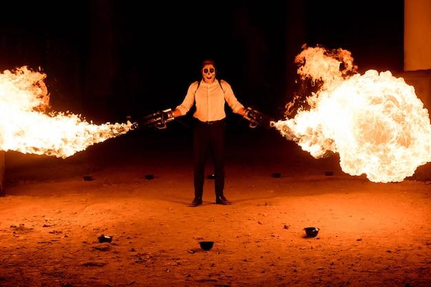 Homem de halloween em traje com lança-chamas nas mãos dele. maquiagem diabo no rosto