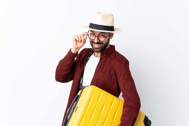 Homem de homem viajante com barba segurando uma mala sobre branco com óculos e sorrindo
