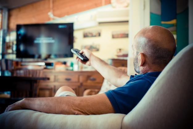Homem de idade miggle assistindo tv