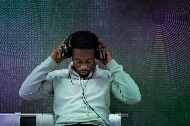 Homem de inovação de gadget musical usando mídia remixada de tecnologia de entretenimento de fone de ouvido