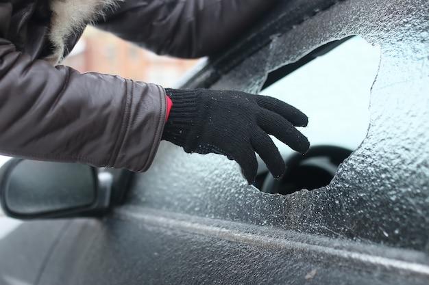 Homem de inverno vandalismo quebrou o vidro do carro uma pedrinha