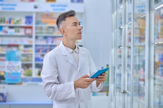 Homem de jaleco branco com comprimido na farmácia